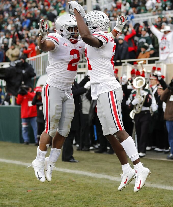 Ohio State wide receiver Parris Campbell, right, and running back J.K. Dobbins (2) celebrate after Campbell's 1-yard touchdown during the first half of an NCAA college football game against Michigan State, Saturday, Nov. 10, 2018, in East Lansing, Mich. (AP Photo/Carlos Osorio)