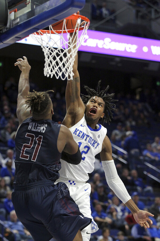 FILE - Kentucky's Keion Brooks Jr. (12) dunks near Fairleigh Dickinson's Elyjah Williams (21) during the second half of an NCAA college basketball game in Lexington, Ky., in this Saturday, Dec. 7, 2019, file photo. The No. 10 Wildcats lost five starters among nine departures from last season including Southeastern Conference Player of the Year Immanuel Quickley and All-SEC first teamer Nick Richards. That left sophomore forward Keion Brooks Jr. as the lone returning regular after starting six of 31 games.(AP Photo/James Crisp, File)