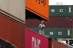 A staff member checks cargos at a port of Kwai Tsing Container Terminals in Hong Kong, Friday, May 24, 2019. Kwai Tsing Container Terminals is one of the busiest ports in the world. (AP Photo/Kin Cheung)