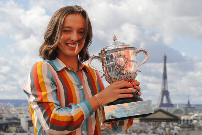 FILE - Poland's Iga Swiatek, poses with the French Open women's singles trophy on a rooftop with the Eiffel Tower in the background in Paris, in this Sunday, Oct. 11, 2020, file photo. It's understandable if names such as skateboarder Sky Brown, Denver Nuggets center Bol Bol or French Open champion Iga Swiatek don't ring an instant bell. Just wait, though. By the time 2021 ends, they could be making an even bigger name for themselves. (AP Photo/Christophe Ena, File)