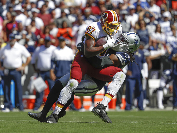 Washington Redskins tight end Jeremy Sprinkle (87) is taken down by Dallas Cowboys middle linebacker Jaylon Smith (54) in the first half of an NFL football game, Sunday, Sept. 15, 2019, in Landover, Md. (AP Photo/Evan Vucci)