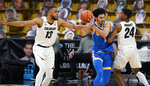 UCLA guard Jules Bernard, center, drives between Colorado forward Dallas Walton, left, and guard Eli Parquet during the second half of an NCAA college basketball game Saturday, Feb. 27, 2021, in Boulder, Colo. (AP Photo/David Zalubowski)