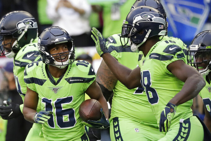 Seattle Seahawks wide receiver Tyler Lockett (16) is greeted by wide receiver Jaron Brown, right, after Lockett scored a touchdown against the Los Angeles Rams during the first half of an NFL football game Thursday, Oct. 3, 2019, in Seattle. (AP Photo/Elaine Thompson)