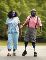 Home health aide Joyce Barnes walks with one of her patients Gregory Gadsden Tuesday, June 30, 2020 in Richmond, Va. The coronavirus pandemic has raised the stakes for Barnes, 61, who cares for Medicaid patients in their homes but does not have health insurance or paid sick leave or hazard pay to care for herself if she contracts COVID-19. (Alexa Welch Edlund/Richmond Times-Dispatch via AP)