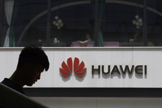 FILE - In this Thursday, May 16, 2019 file photo, a man is silhouetted near the Huawei logo in Beijing. Lithuanian cybersecurity authorities are urging the country's governmental agencies to abandon the use of Chinese smartphone brands. Lithuania's National Cyber Security Center said Tuesday, Sept. 21, 2021 it found four major cybersecurity risks for devices made by Huawei and Xiaomi. (AP Photo/Ng Han Guan, file)