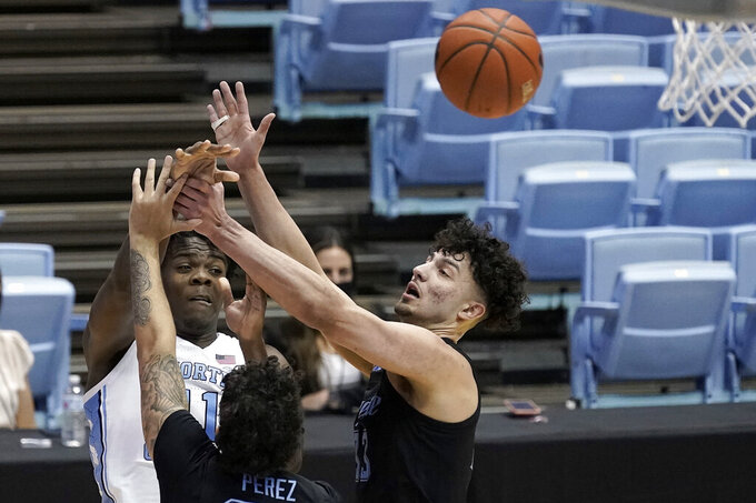 North Carolina forward Day'Ron Sharpe (11) passes the ball past Marquette forward Dawson Garcia (33) and guard Jose Perez during the first half of an NCAA college basketball game in Chapel Hill, N.C., Wednesday, Feb. 24, 2021. (AP Photo/Gerry Broome)