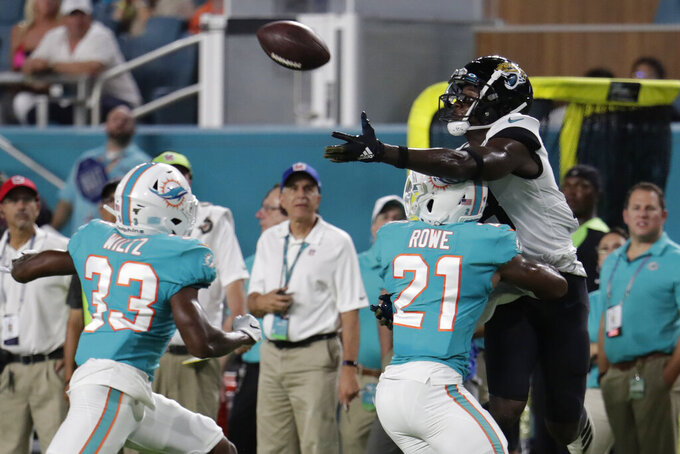 Jacksonville Jaguars wide receiver Chris Conley, right, attempts to catch a pass as he is guarded by Miami Dolphins cornerback Eric Rowe (21) and cornerback Jomal Wiltz (33) during the first half of an NFL football preseason game Thursday, Aug. 22, 2019, in Miami Gardens, Fla. (AP Photo/Lynne Sladky)