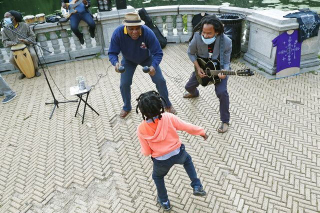 In this Tuesday, June 16, 2020, photo, musician Alix Julien, above, center, encourages 6-year-old Nova Sankara to dance as Alegba Jahyile, right, leads the band Alegba and Friends in a nightly concert at Brooklyn's Prospect Park boathouse in New York. In pre-COVID-19 days, the band performed in local bars and restaurants. But since the pandemic, indoor restaurant dining has been suspended, so the group has taken their music outdoors by the water's edge where they've developed a loyal following of regulars. Sankara's father is a professional dancer. (AP Photo/Kathy Willens)