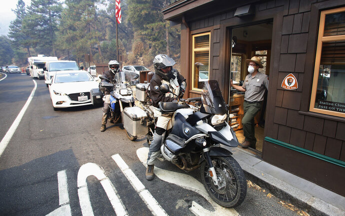 Park Ranger Alex Martinez passes maps out and directs visitors at the Highway 140 gate as Yosemite National Park reopens in California, Tuesday, Aug. 14, 2018. The nearly three-week closure was the result of a wildfire. (AP Photo/Gary Kazanjian)