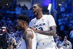 Xavier's Naji Marshall (13) celebrates with Tyrique Jones, left, during the second half of an NCAA college basketball game against Cincinnati, Saturday, Dec. 7, 2019, in Cincinnati. (AP Photo/John Minchillo)