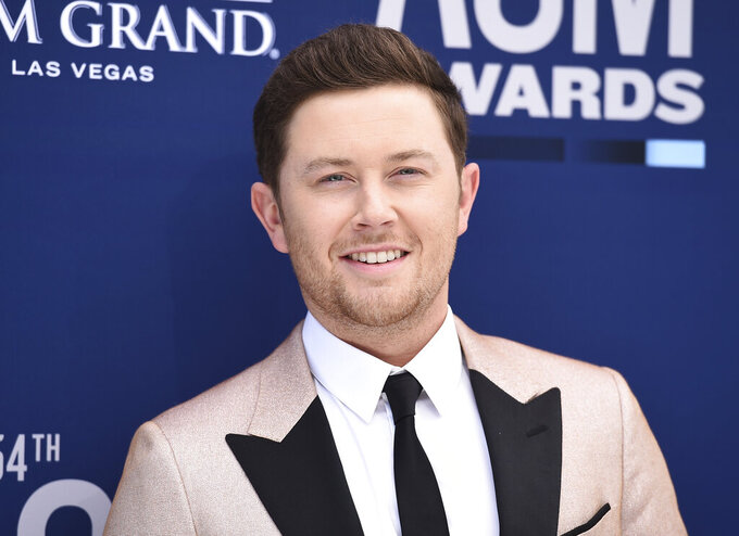 """FILE - In this April 7, 2019, file photo, Scotty McCreery arrives at the 54th annual Academy of Country Music Awards at the MGM Grand Garden Arena in Las Vegas. A decade ago, McCreery won """"American Idol."""" At age 17. So the country music star and huge NFL fan knows all about the pressure players face. Maybe even more so: Remember, as well as he might have performed on stage, fans across the country were casting votes for who would win the competition. Not exactly something in McCreery's control. (Photo by Jordan Strauss/Invision/AP, File)"""