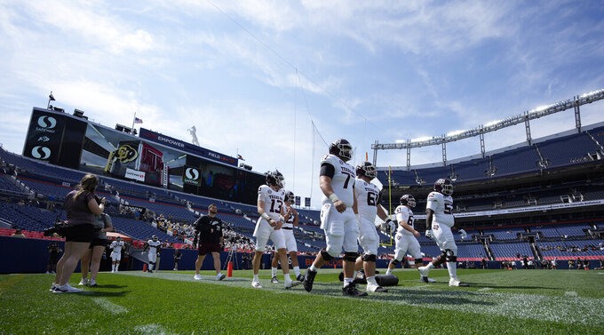 Texas A&M players take the field to warm up before the first half of an NCAA college football game against Colorado, Saturday, Sept. 11, 2021, in Denver. (AP Photo/David Zalubowski)