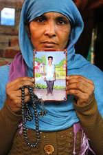 In this Tuesday, Dec. 24, 2019, photo, the mother of Mohammad Asif who was shot and killed during protests against Citizenship Amendment Act, holds a photograph of him at her residence in Meerut, India. Tens of thousands of people have taken to the streets to oppose a new law that grants a path to citizenship for immigrants of every religion except Islam. Many say the law, passed by Prime Minister Narendra Modi's Hindu-nationalist government, discriminates against Muslims and undermines the country's secular foundations. (AP Photo/Rajesh Kumar Singh)