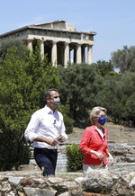 Greek Prime Minister Kyriakos Mitsotakis, left, and European Commission President Ursula von der Leyen, walk in front of the Temple of Hephaestos during an event at the Ancient Agora in Athens, Thursday, June 17, 2021. (Louiza Vradi/Pool via AP)