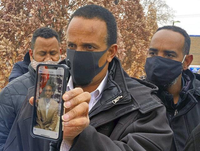 Bayle Gelle, of Eden Prairie, holds a phone with a photo of his 22-year-old son, Dolal Idd, in south Minneapolis on Thursday, Dec. 31, 2020. Police in Minneapolis said they would release body camera video on Thursday, from a traffic stop that ended with Idd's death, the city's first police-involved death since George Floyd died while being restrained by officers in May. (Chao Xiong/Star Tribune via AP)