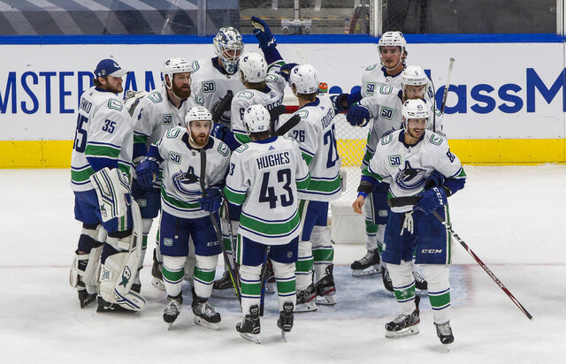 Vancouver Canucks celebrate  win over the St. Louis Blues in Game 5 of an NHL hockey first-round playoff series in Edmonton, Alberta, Wednesday, Aug. 19, 2020. (Jason Franson/The Canadian Press via AP)