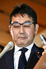 Japanese Justice Minister Katsuyuki Kawai looks down, surrounded by reporters, after submitting his resignation to Prime Minister Shinzo Abe at Abe's official residence in Tokyo Thursday, Oct. 31, 2019.  Kawai resigned over election fraud allegations involving his wife, also a lawmaker, and about his own gift-giving allegations reported in a tabloid magazine. (Yoshitaka Sugawara/Kyodo News via AP)