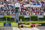 Kyle Busch (18) takes the checker flag to win the NASCAR Cup Series auto race at Pocono Raceway, Sunday, June 27, 2021, in Long Pond, Pa. (AP Photo/Matt Slocum)