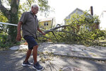 A man makes his way down a street in Queens where a tree fell on top of a house, downing power lines in the area in the wake of Tropical Storm Isaias, Wednesday, Aug. 5, 2020, in the Queens borough of New York. The storm passed through the area Tuseday afternoon as it made it's way up the East coast of the United States. (AP Photo/Kathy Willens)