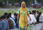FILE - In this May 27, 2019 file photo, a Pakistani transgender person provides food to people during the Muslim fasting month of Ramadan, in Islamabad, Pakistan, Monday, May 27, 2019. Pakistan has begun issuing special health care cards for transgender people. They have often been denied treatment because doctors could not decide whether to treat them in a male or female ward. (AP Photo/B.K. Bangash,file)