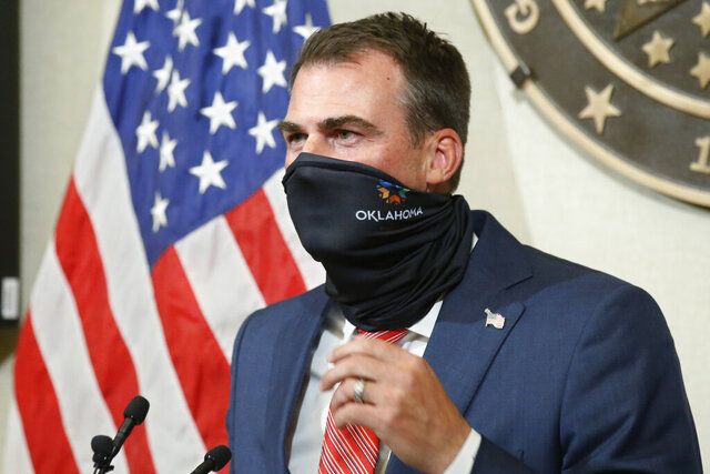 Oklahoma Gov. Kevin Stitt demonstrates how easy it is to wear a face mask during a news conference, Tuesday, June 30, 2020, in Oklahoma City. (AP Photo/Sue Ogrocki)