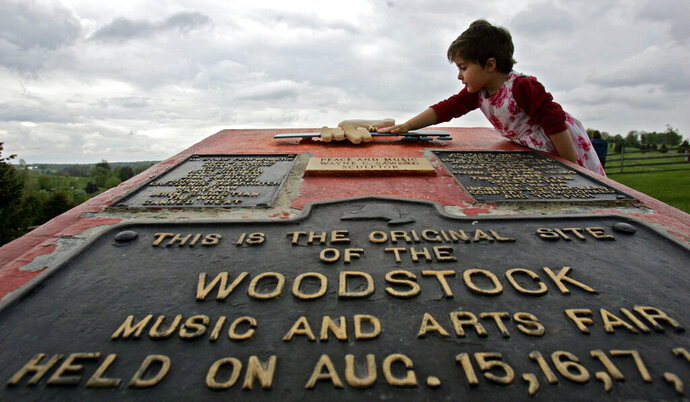FILE - This May 15, 2008 file photo shows Emma Cenholt, 3, of Trumbull, Conn., playing on a memorial at the site of the Woodstock Music and Arts Fair in Bethel, N.Y. The Woodstock 50 festival is back on after a court on Wednesday, May 15, 2019, rebuffed an ex-investor's effort to cancel the anniversary extravaganza. But organizers will have to do without some $18 million, at least for now. (AP Photo/Mike Groll, File)