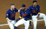 Minnesota Twins' Byron Buxton, center, celebrates his winning RBI-single off Detroit Tigers pitcher Jose Cisnero with Josh Donaldson, left, and Jorge Polanco in the ninth inning of a baseball game Saturday, Sept. 5, 2020, in Minneapolis. (AP Photo/Jim Mone)