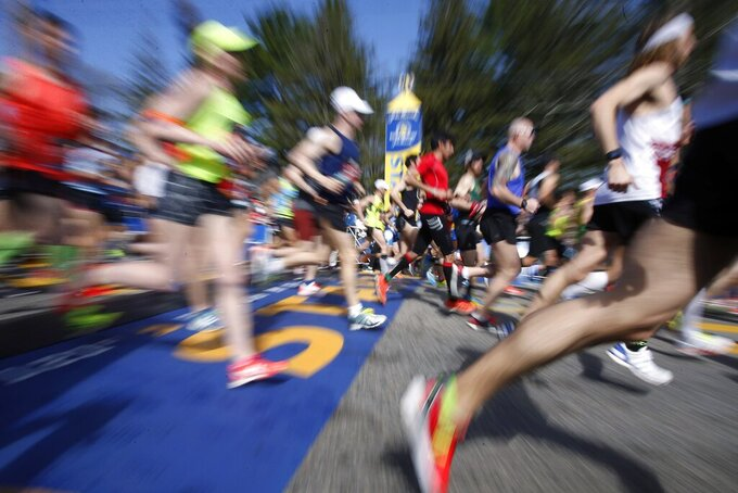 FILE - In this April 17, 2017, file photo, runners cross the Boston Marathon start line in Hopkinton, Mass. The 124th Boston Marathon is scheduled for Monday, April 20, 2020. Boston Marathon organizers say they're postponing the prestigious race until Sept. 14 because of concerns over the coronavirus pandemic. (AP Photo/Mary Schwalm, File)