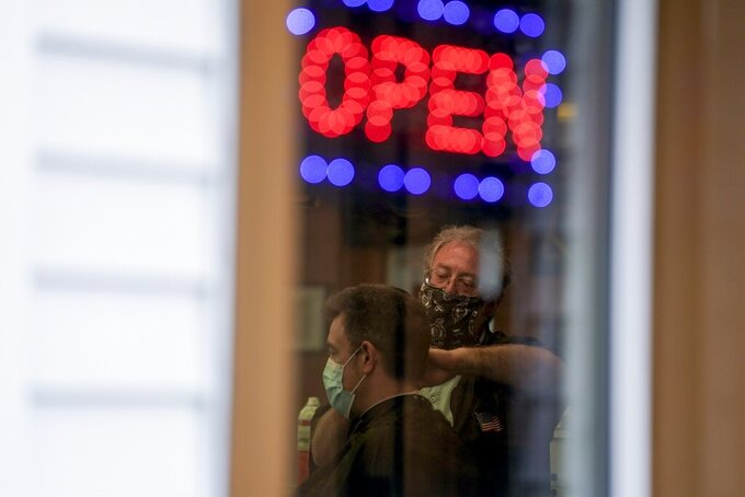 Owner Paul Furrer cuts the hair of Jeff Jones at Rich's Barber Shop on Thursday, May 14, 2020, in Waukesha, Wis. The store re-opened after the Wisconsin Supreme Court struck down Gov. Tony Evers' stay-at-home order Wednesday. (AP Photo/Morry Gash)