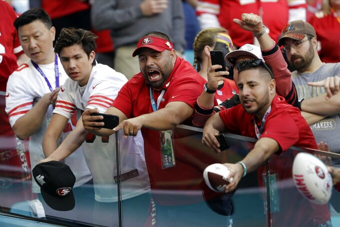 Fans react while watching warm ups before the NFL Super Bowl 54 football game between the San Francisco 49ers and Kansas City Chiefs Sunday, Feb. 2, 2020, in Miami Gardens, Fla. (AP Photo/John Bazemore)
