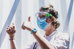 """A staffer wearing a mask gives the thumb-up sign aboard the Ocean Viking ship in the Mediterranean Sea, Sunday, July 5, 2020.  A humanitarian group says its rescue ship with 180 migrants stranded aboard for days has """"finally"""" received instructions to sail to an Italian port, so its passengers can be disembarked. SOS Mediterranee in a tweet on Sunday also described """"relief on the #Ocean Viking"""" when the ship's crew and passengers learned that the rescued migrants are to be disembarked at Porto Empedocle, Sicily, the next day. (Flavio Gasperini/SOS Mediterranee via AP)"""