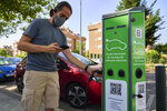 A man charges his electric car at an electrical charging point in Rivas Vaciamadrid, Spain, Tuesday, June 15, 2021.  Spain is Europe's second-leading car maker but it is lagging behind when it comes to electric cars, a situation that the government aims to change by using around five billion euros of the EU pandemic recovery funds to kickstart the electric car industry. The government plans to spend big, to install a network of public recharging stations and to convince customers about the benefits of buying electric or hybrid vehicles. (AP Photo/Manu Fernandez)