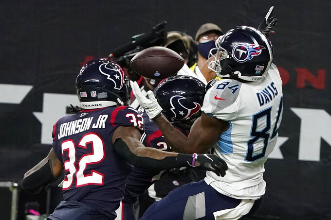 Tennessee Titans wide receiver Corey Davis tries to make a catch as he is hit by Houston Texans cornerback Vernon Hargreaves III, center, during the second half of an NFL football game Sunday, Jan. 3, 2021, in Houston. The pass was incomplete. (AP Photo/Eric Christian Smith)