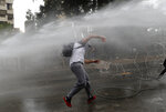 A Hezbollah supporter is sprayed by a water canon as he throws stones at riot police during a protest against U.S. interference in Lebanon's affairs, near the U.S. embassy, in Aukar northeast of Beirut, Lebanon, Friday, July 10, 2020. (AP Photo/Hussein Malla)