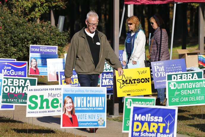Voters walk through a sea of campaign signs at a polling station in Richmond, Va., Tuesday, Nov. 5, 2019. All seats in the Virginia House of Delegates and State senate are up for election. (AP Photo/Steve Helber)