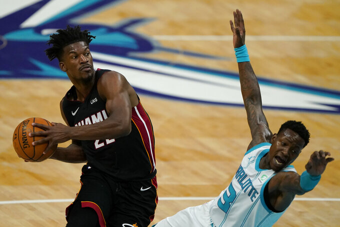 Miami Heat forward Jimmy Butler drives to the basket past Charlotte Hornets guard Terry Rozier during the first half of an NBA basketball game on Sunday, May 2, 2021, in Charlotte, N.C. (AP Photo/Chris Carlson)