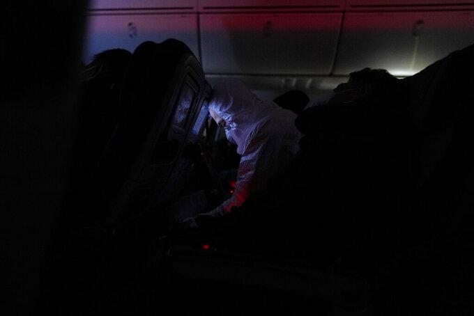 A passenger sleeps on a flight from Buenos Aires to Frankfurt, Germany, Sunday, July 18, 2021. (AP Photo/Natacha Pisarenko)