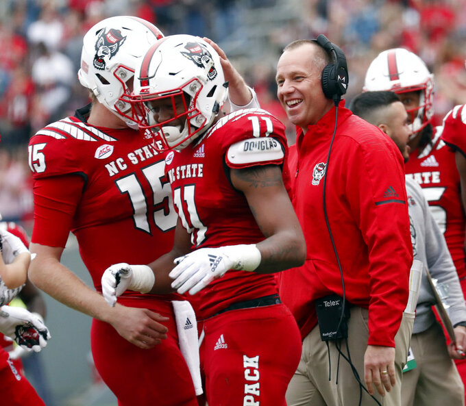 North Carolina State's Jakobi Meyers (11) celebrates his touchdown with Ryan Finley (15) and head coach Dave Doeren during the first half of NCAA college football game in Raleigh, N.C., Saturday, Dec. 1, 2018. (AP Photo/Chris Seward)