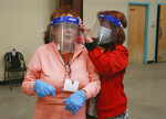 Poll workers Patricia Gurule, left, and Maria Britto, right, put on personal protective equipment as early voting starts at the county fair building on Saturday, Oct. 17, 2020, in Santa Fe, N.M. Hundreds lined up Saturday to vote in person or drop off absentee ballots as part of the 2020 presidential election. (AP Photo/Cedar Attanasio)