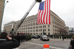 The Milwaukee Fire Department raises a flag at the intersection of 9th and State streets as the hearse containing the casket of a Milwaukee police officer drives under in Milwaukee on Wednesday, Feb. 6, 2019. The 17-year police veteran was shot and killed as he served a warrant on Milwaukee's south side Wednesday, becoming the city's third officer to be killed in the line of duty in eight months, officials said. The 35-year-old officer's name has not been released at the time of this reporting. (James B. Nelson/Milwaukee Journal-Sentinel via AP)