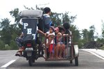 Residents ride a pedicab as they evacuate to higher grounds in preparation for the coming of Typhoon Kammuri in Legazpi, Albay province, southeast of Manila, Philippines on Monday Dec. 2, 2109. The Philippines' main island, including the national capital, Manila, is under a tropical cyclone warning for a typhoon forecast to hit Monday night into Tuesday. (AP Photo)