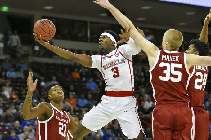 Mississippi's Terence Davis (3) shoots past Oklahoma's Brady Manek (35) and Kristian Doolittle (21) during a first-round game in the NCAA men's college basketball tournament in Columbia, S.C. Friday, March 22, 2019. (AP Photo/Richard Shiro)