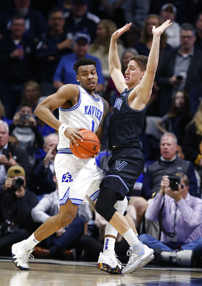 Xavier guard Paul Scruggs, left, is pressured by Villanova guard Collin Gillespie, right, during the second half of an NCAA college basketball game, Saturday, Feb. 22, 2020, in Cincinnati. (AP Photo/Gary Landers)