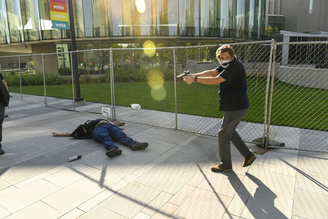 FILE - This Oct. 10, 2020 file photo shows security guard Matthew Dolloff, right, after fatally shooting