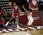 Alabama's John Petty Jr. (23) throws the ball away from Oklahoma's Elijah Harkless (24) during the second half of an NCAA college basketball game in Norman, Okla., Saturday, Jan. 30, 2021. (AP Photo/Garett Fisbeck)