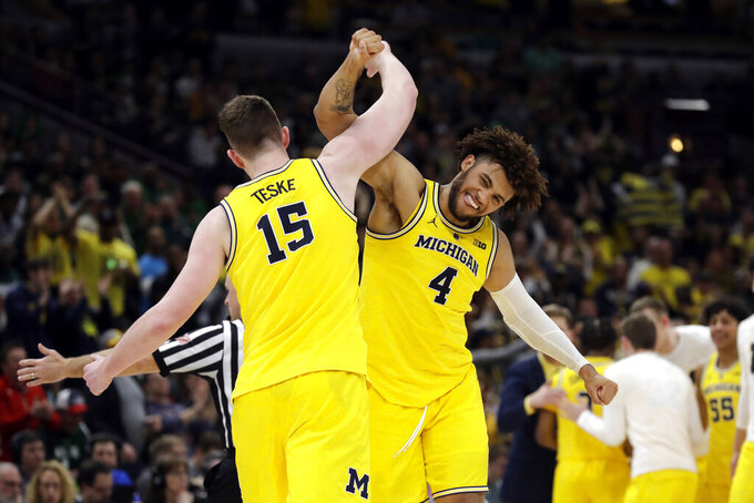 Michigan's Jon Teske (15) and Isaiah Livers (4) celebrate during the second half of an NCAA college basketball championship game against Michigan State in the Big Ten Conference tournament, Sunday, March 17, 2019, in Chicago. (AP Photo/Nam Y. Huh)