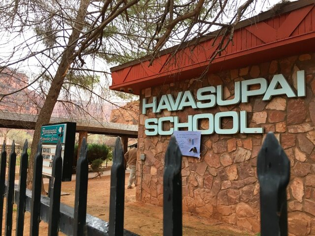 FILE - In a Saturday, Feb. 17, 2018 file photo, a fence surrounds Havasupai Elementary School in Havasupai, Ariz. A lawsuit that accuses the federal government of failing to adequately provide for students on a small, isolated reservation in Arizona is set to go to trial in November. The lawsuit filed in 2017 seeks systematic reforms of the U.S. Bureau of Indian Education, an agency that oversees more than 180 schools in nearly two dozen states but directly operates less than one-third of them.(Alden Woods/The Arizona Republic via AP,File)