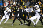 Appalachian State quarterback Zac Thomas (12) looks for an open receiver while getting pressure from Georgia Southern linebacker Lane Ecton (7) during the first half of an NCAA college football game Thursday, Oct. 31, 2019, in Boone, N.C. (AP Photo/Brian Blanco)