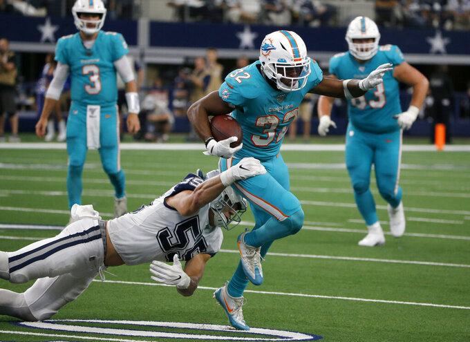 Dallas Cowboys outside linebacker Leighton Vander Esch (55) attempts to stop Miami Dolphins running back Kenyan Drake (32) from gaining extra yardage on a run in the second half of an NFL football game in Arlington, Texas, Sunday, Sept. 22, 2019. (AP Photo/Michael Ainsworth)