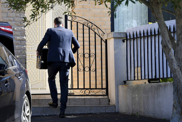 A federal officer enters the home of New South Wales state lawmaker Shaoquett Moselmane in Sydney Friday, June 26, 2020. Moselmane was suspended from his party Friday and his home was searched in an investigation of alleged influence by China. Police and intelligence officers searched his Sydney home and also had a warrant for his parliamentary offices, said state Labor leader Jodi McKay.  (Bianca De Marchi/AAP Image via AP)